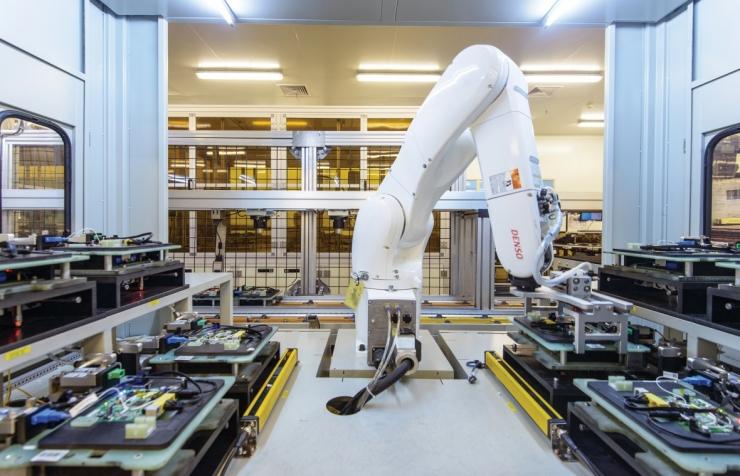 一个机器人臂正在移动电路板进行各种测试.